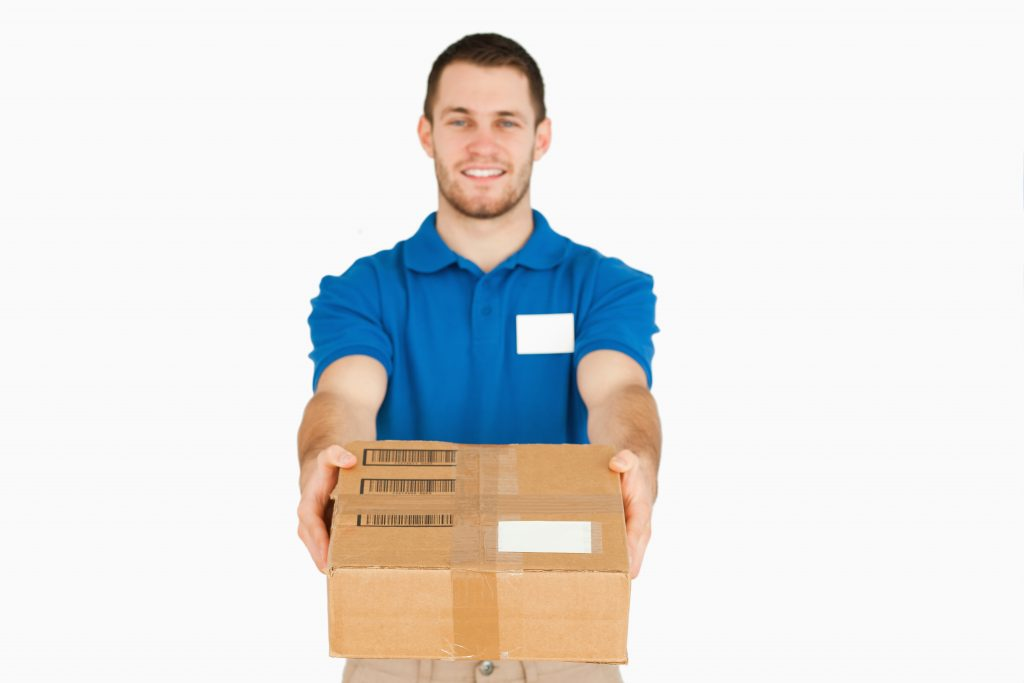 Smiling young sales assistant handing over parcel